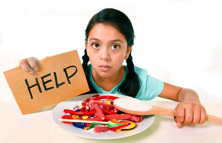 Jeune fille polynésienne qui tient une pancarte sur laquelle il est inscrit le mot HELP assise devant une assiette de bonbons.