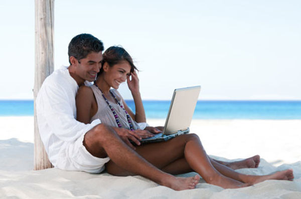 Un couple sur la plage avec un ordinateur portable