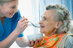 a carer helping an elderly lady eating