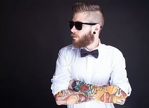 Hipster Man with tattoed arms crossed looking right