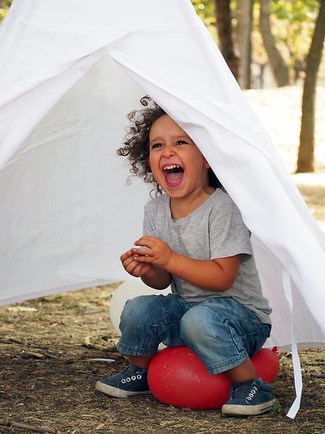 Happy kid in a teepee щастливо дете в типи палатка