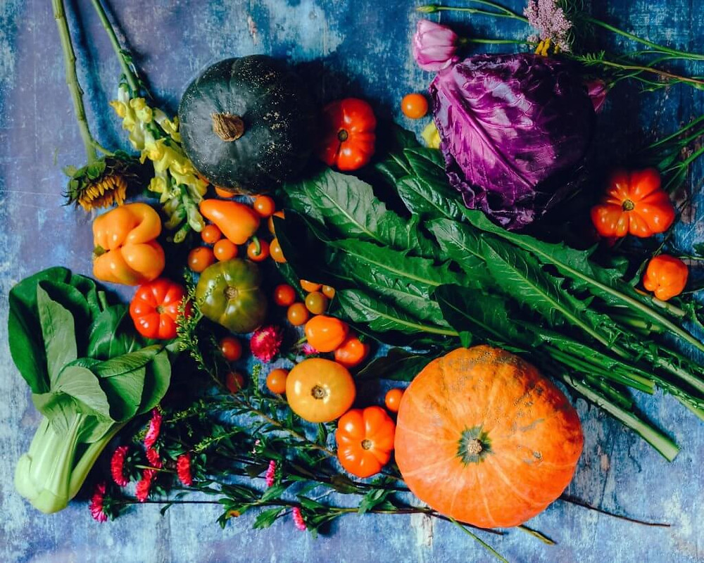 Fresh fruits, vegetables, and spring flowers on a grey background.