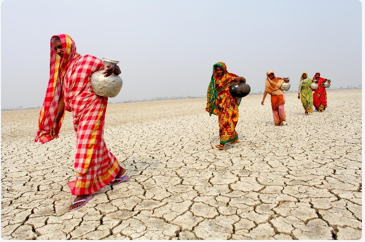 women walking over desert area. impact of drought