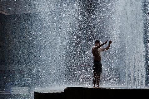 man showering in a plaza in prague