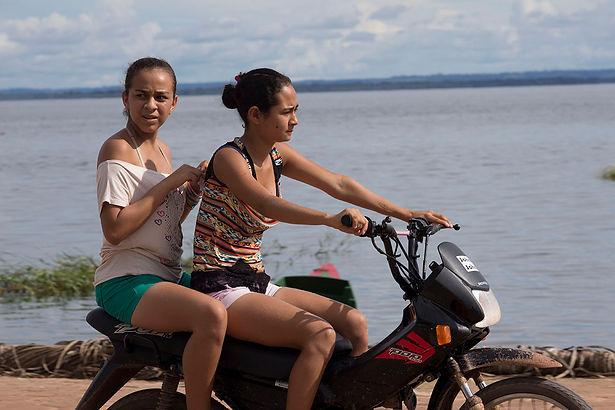 Girls riding a bike in Xingu, Amazonia
