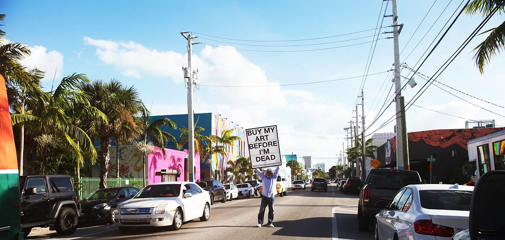 """Photo of artist Alvaro José holding a sign that reads """"BUY MY ART BEFORE I'M DEAD"""" in the middle of the street in Wynwood Arts District in the city of MIami"""