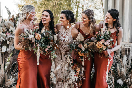 boho bridesmaids in rust dresses with dried flower bouquets