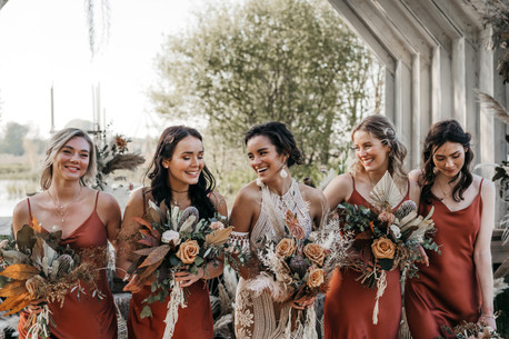 bohemian bridesmaids in rust dresses with dried flower bouquets
