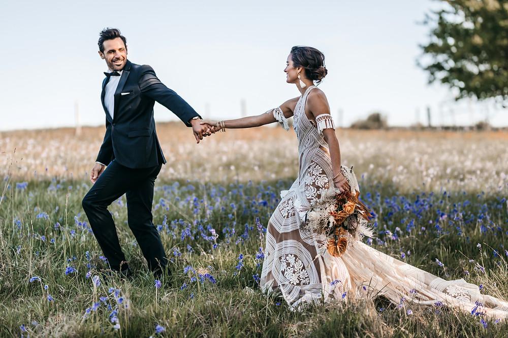Bride and groom walking through bluebell field at wilderness weddings venue in Kent