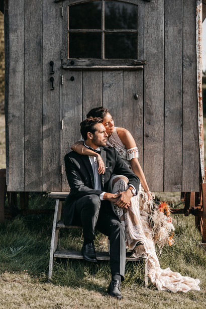 Bride and groom with a shepherd's hut at wilderness weddings venue in Kent