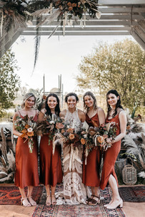 bohemian bridesmaids in rue de seine and rust dresses with dried flower bouquets
