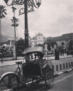 A becak driver takes a break with the Bank Indonesia and Post Office in the background