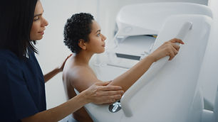 Friendly Female Doctor Explains the Mammogram Procedure to a Topless Latin Female Patient
