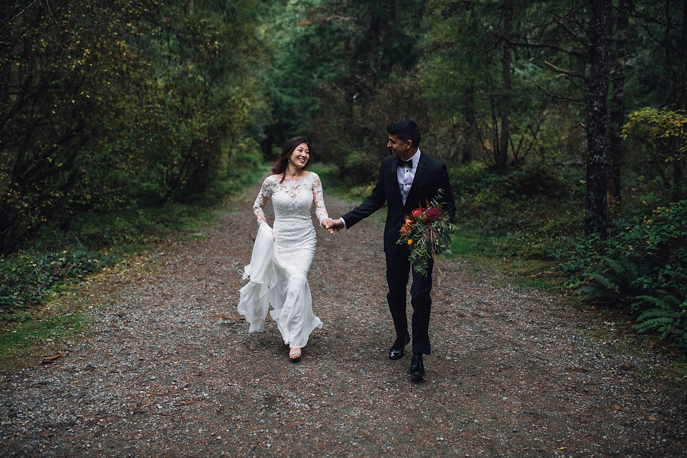Couple running together in wedding attire in forest