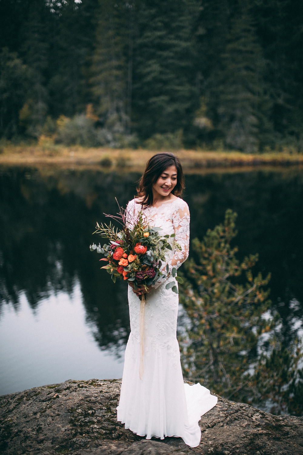 bride posing in front of beautiful lake with flowers