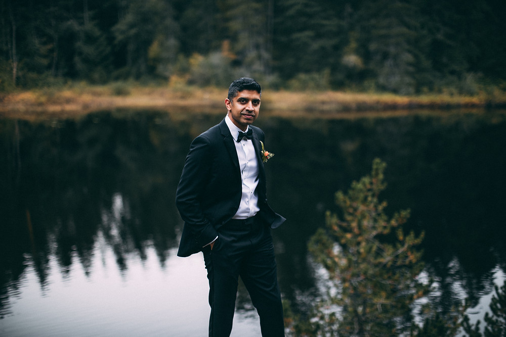 groom standing in front of lake in suit