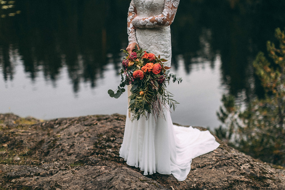 bride holding bouquet of flowers standing in front of lake