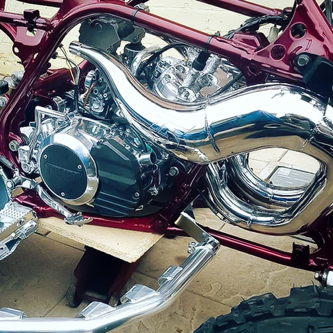Quad bike engine and exhaust to mirror.