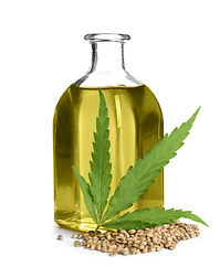 Bottle with hemp oil, leaf and seeds on