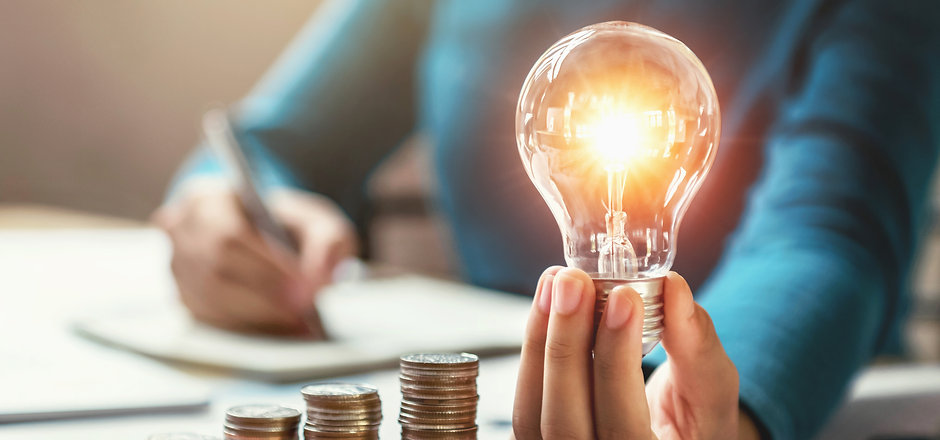 business woman hand holding lightbulb with coins stack on desk. concept saving energy and