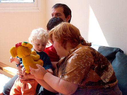 ילד בן שנתיים על בירכי אביו משחק בבובה עם אישה עם מוגבלות שכלית