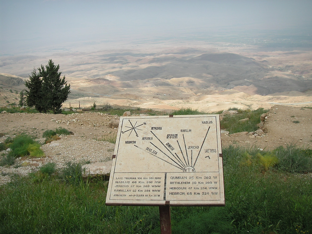 View from Mount Nevo on the Land of Israel. The sign details the direction and distance to the big cities.
