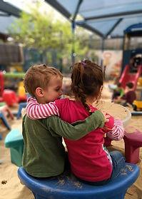 ילדה וילד בגיל גן יושבים מחובקים