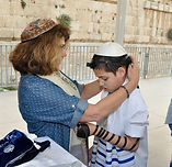 Rabbi Kinneret Armor helps a child with a disability to put on Tefillin