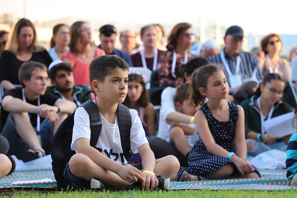 Children sitting on the grass with a crowd in the background at the IMPJ's 2018 Biennial