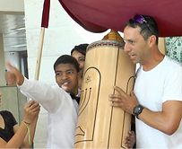 A child with intellectual disabilities holding the Torah and motions with thumb up