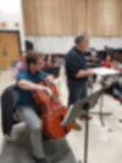 An image of Josh playing the cello in a rehearsal