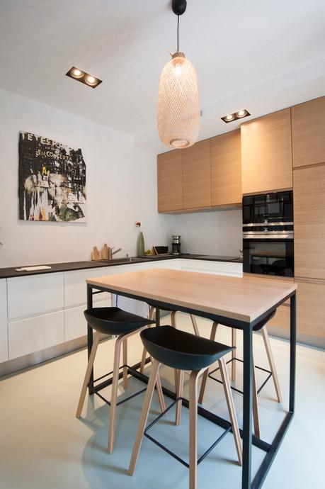 Une cuisine qui associe le blanc, le noir et le chène