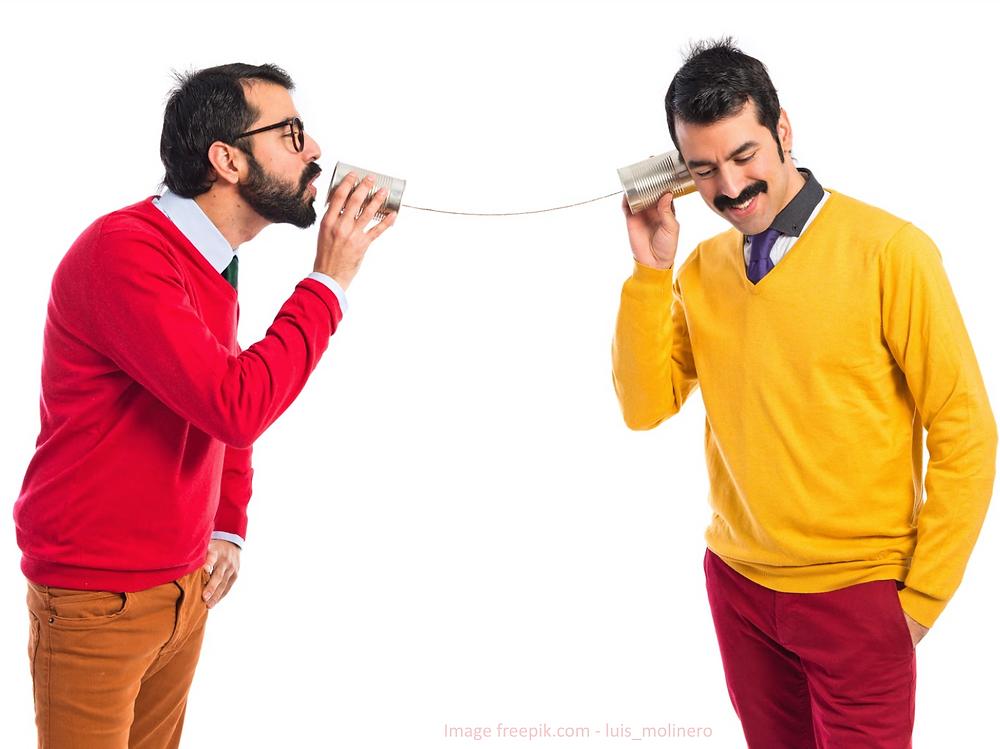 Deux hommes qui communiquent au travers d'un dispositif de boîtes de conserve pour illustrer la difficulté de la communication interpersonnelle