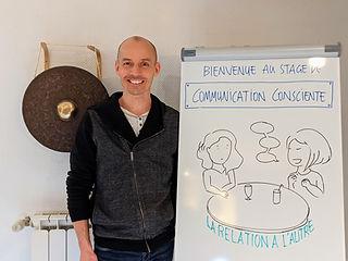 Olivier Babando à côté d'un tableau blanc de présentation de son stage de communication consciente (inspirée de la CNV)