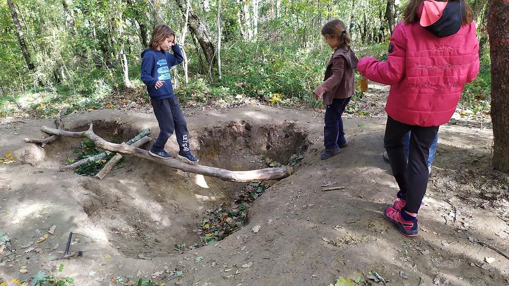 une enfant traverse un trou sur une branche