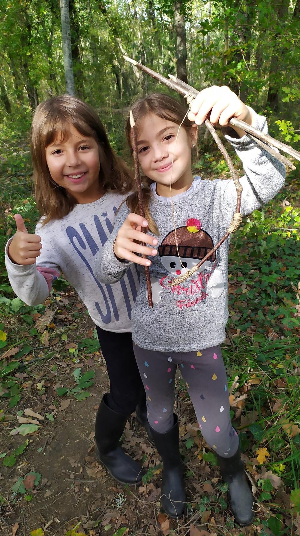 deux enfants avec des bouts de bois et de la ficelle