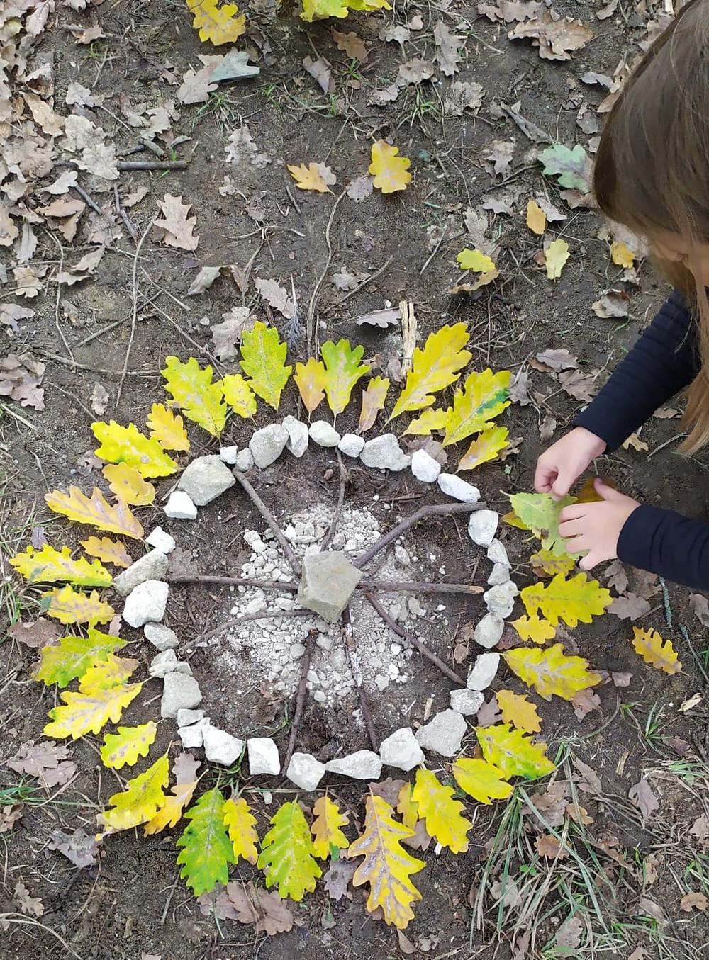 cercle de cailloux et de feuille fait par un enfant