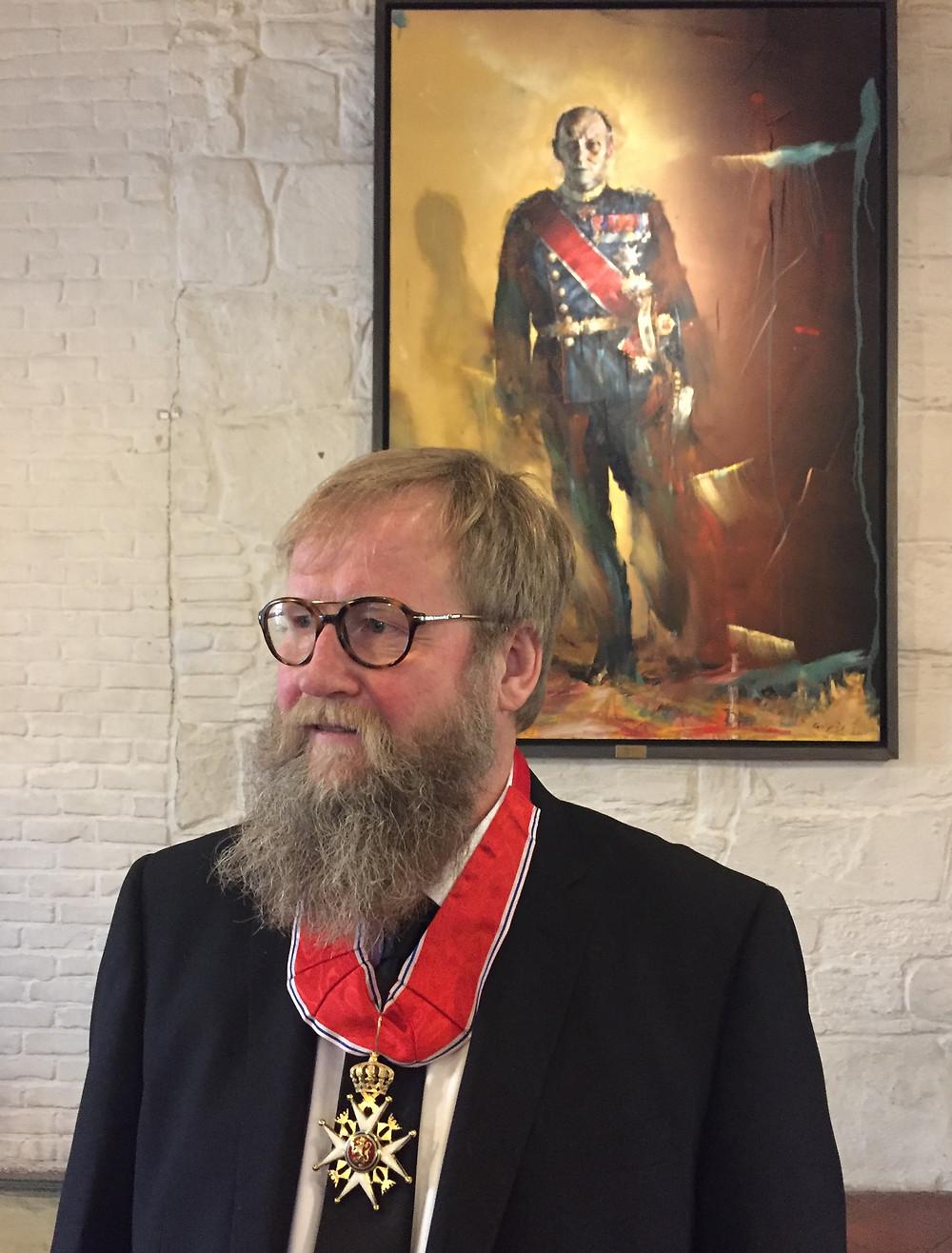 Håkon Gullvåg foran sitt maleri av kong Harald V i Erkebispegården i Trondheim, under overrekkelsen av ordenstegnet som kommandør av St. Olavs Orden 30. januar 2016 Foto: Steinar Larsen