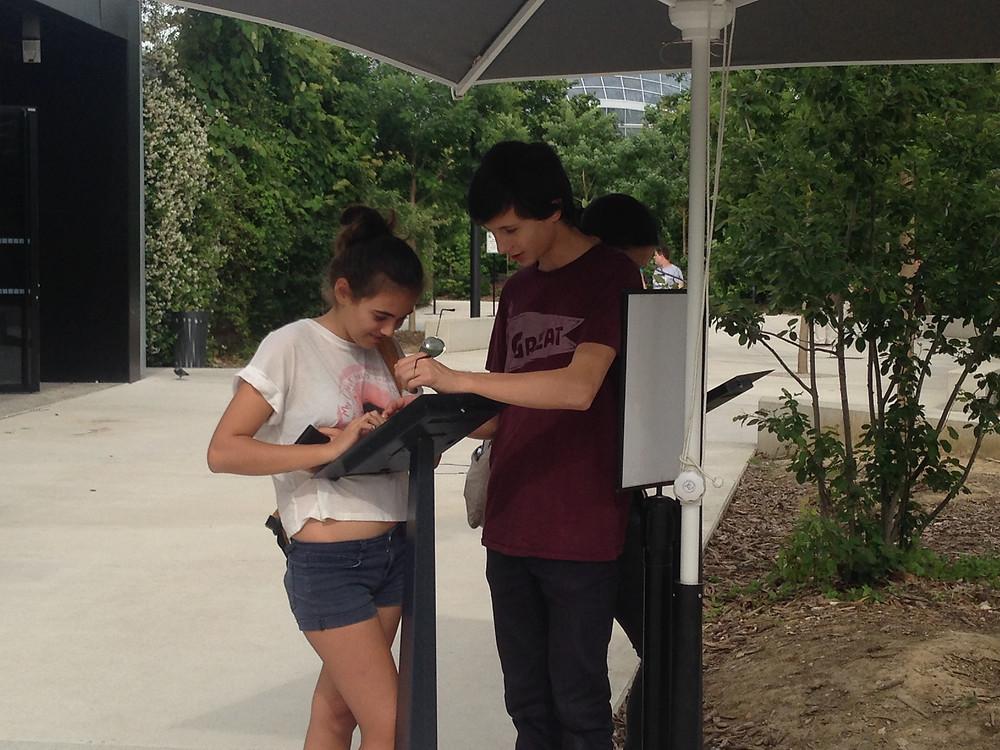 Adolescents laissant un avis sur le livre d'or digital du parc zoologique de Paris