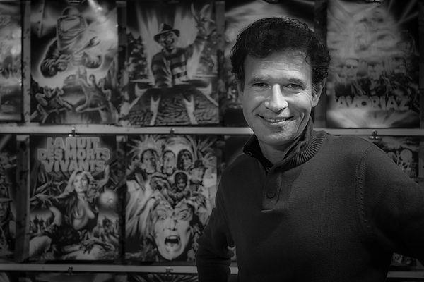 Laurent Melki illustrateur affiches d'horreur au 10ème festival Européen du film fantastique de Strasbourg, devant ses affiches d'horreur cultes: Freddy, La nuit des morts vivants, Mad movies, avoriaz. Site d horreur, site de film d'horreur, horreur