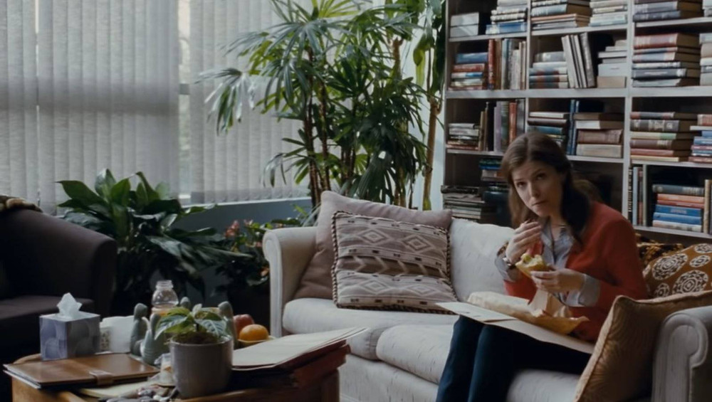 Katherine McKay, played by actress, Anna Kendrick, in the movie 50/50, eats a sandwich as someone enters the room