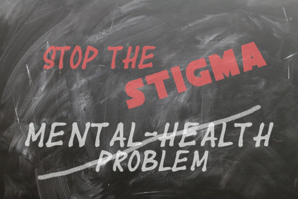 A dirty chalkboard that reads: Stop The Stigma, with the words Mental Health Problem crossed out