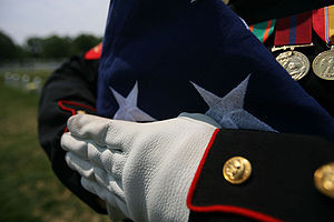 English: A folded American flag held by a Unit...