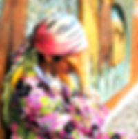 Picture of a woman in colorful garb sitting on a sidewalk in Posadas, Argentina as a fine art print for the wall of your home or office.