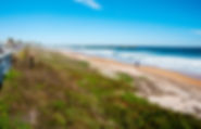 Picture of a man with a metal detector near Flagler Beach, Florida's pier as a fine art print for the wall of your home or office.