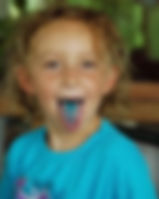 Picture of a young girl sticking out her blue tongue which was caused by drinking blue gatorade as a fine art print for the wall of your home or office.