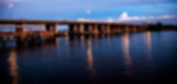 Picture of people fishing on the US 41 bridge in Gibsonton, Florida as the sun sets as a fine art print for the wall of your home or office.