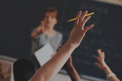 Dans une classe une enseignante interroge un élève qui pose une question en levant la main