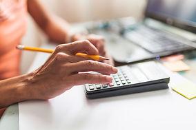 crop-person-making-calculations-near-laptop.jpg