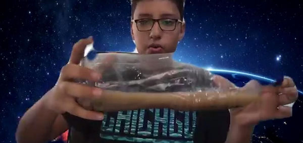 Young pupil with glasses looking at gooish liquid in bottle as part of his Christian science education program